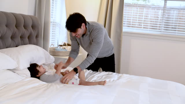 vídeos y material grabado en eventos de stock de padre juega con el niño mientras lo prepara para la hora de acostarse - balancearse