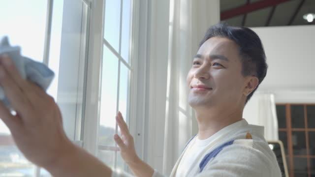 father polishing the glasses of window with towel - 朝鮮半島点の映像素材/bロール