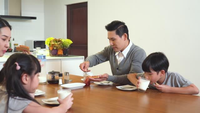 vídeos y material grabado en eventos de stock de padre preparar comida feliz para todos los miembros cuando la familia desayuna juntos - happy meal