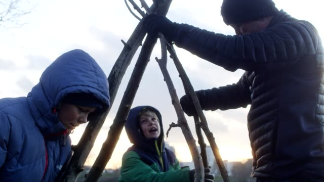 father preparing campfire with sons. riverside in the city - winter coat stock videos & royalty-free footage