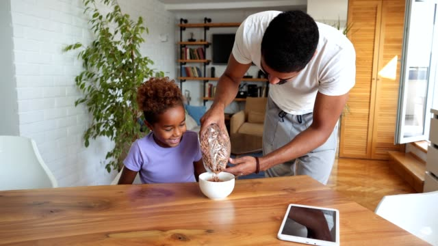 Father preparing chocolate cereal for daughter's breakfast