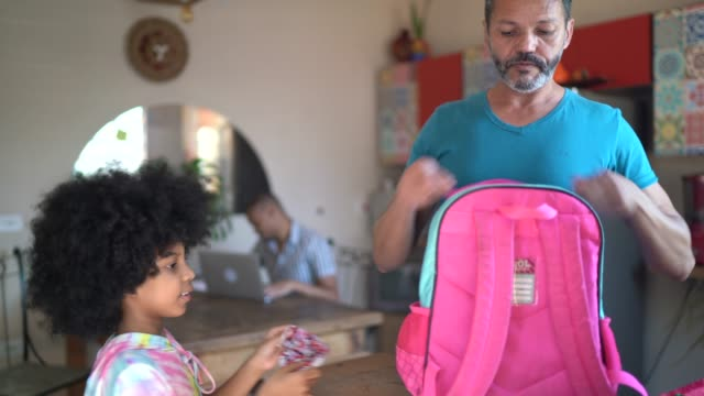 father preparing daughter's backpack for school - school supplies stock videos & royalty-free footage