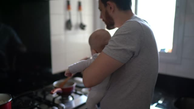 father preparing lunch with his son on his lap - modern manhood stock videos & royalty-free footage
