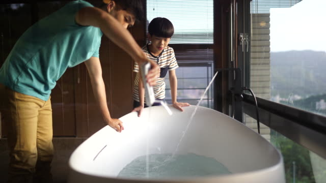 father preparing the bathtub for his son - wellbeing stock videos & royalty-free footage