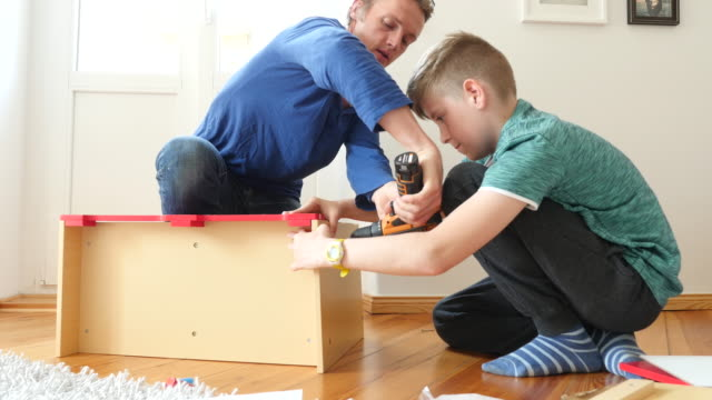 Father preparing toy kitchen with son at home