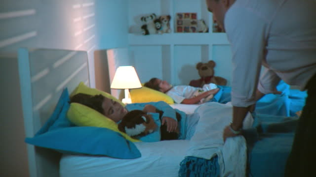 ms father pulling duvet up and kissing sleeping daughter good night then turning light off, panama city, panama  - ora di andare a letto video stock e b–roll
