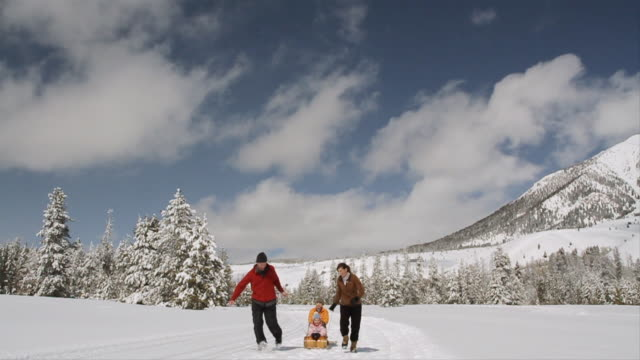 ws slo mo father pulling two small children on toboggan and mother running behind / sun valley, idaho, united states - idaho stock videos & royalty-free footage