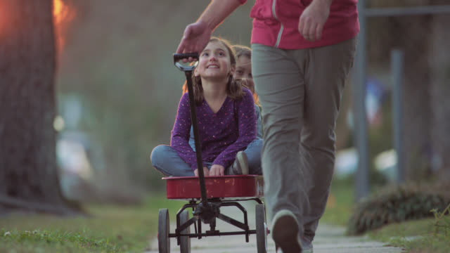 WS SLO MO. Father pulls daughters up neighborhood sidewalk in little red wagon.
