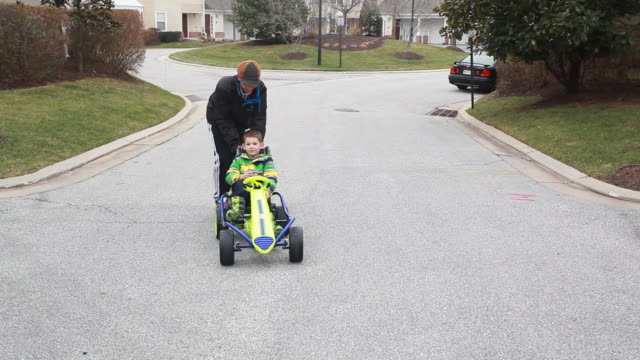 Father pushes boy in gocart down residential street as boy swerves around the road.