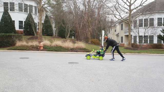 father pushes boy in gocart up a residential street. - kelly mason videos stock videos & royalty-free footage
