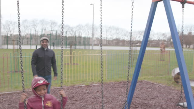 father pushes his son on a park swing - candid stock videos & royalty-free footage