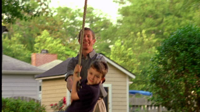 a father pushes his young son on a tire swing in their suburban backyard. - tyre swing stock videos & royalty-free footage