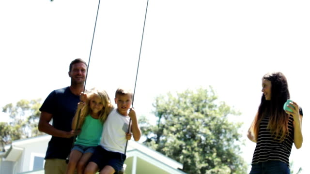 father pushes kids on the swing - swinging stock videos & royalty-free footage