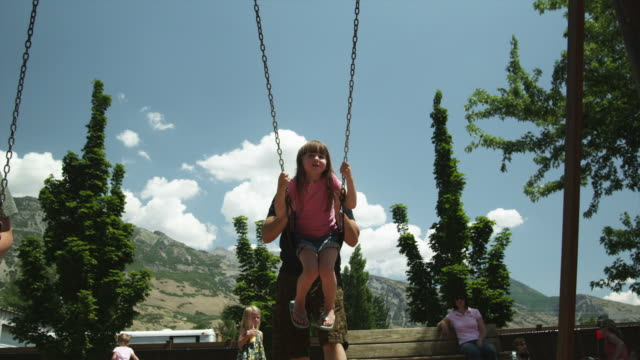 vidéos et rushes de ms father pushing daughter (2-3) in swing in park, american fork, utah, usa - famille monoparentale