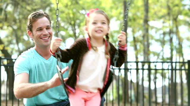 Father pushing daughter on swing in park