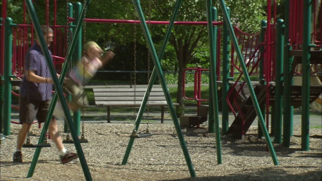stockvideo's en b-roll-footage met ms father pushing daughter on swing set in public park/ fanwood, new jersey - genderblend