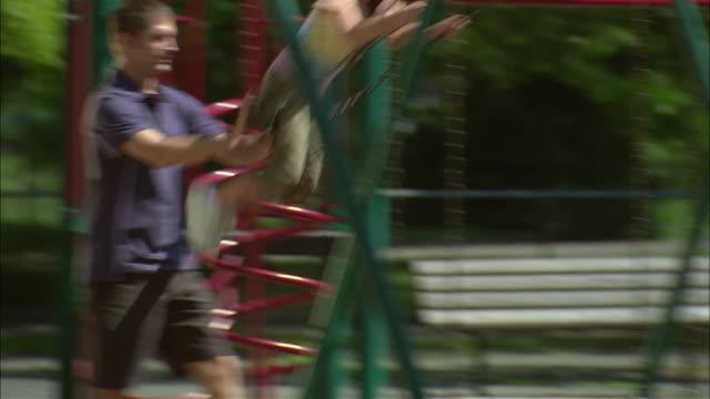 vídeos de stock e filmes b-roll de ms father pushing daughter on swing set in public park/ girl getting off swing/ man sitting down on swing/ fanwood, new jersey - genderblend