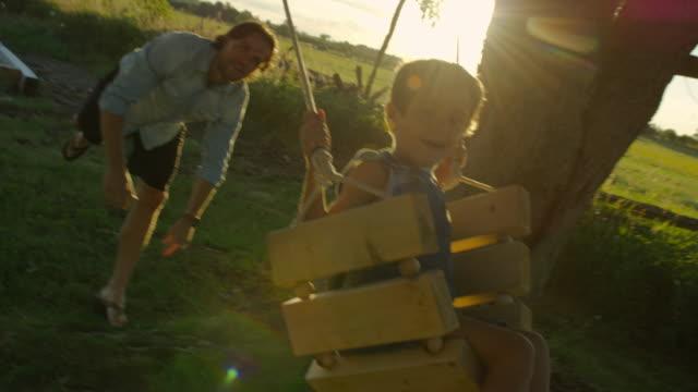 夕暮れ時のスイングの彼の小さい男の子を押すの父 - 継父点の映像素材/bロール