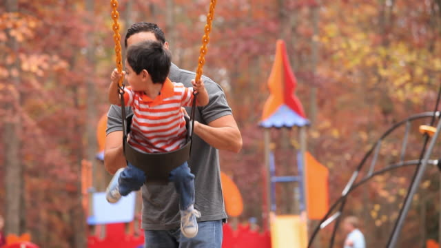 vidéos et rushes de ms father pushing son (2-3) on playground swing / richmond, virginia, usa - balançoire