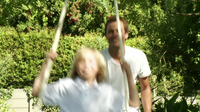 ms father pushing son (8-9) on rope swing, cape town, south africa - rope swing stock videos & royalty-free footage