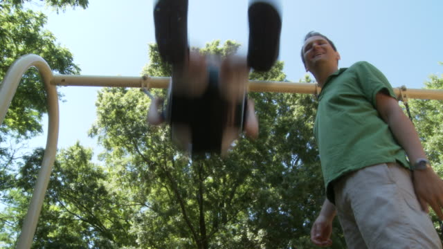 ms father pushing son (2-3) on swing / atlanta, georgia, usa - genderblend video stock e b–roll