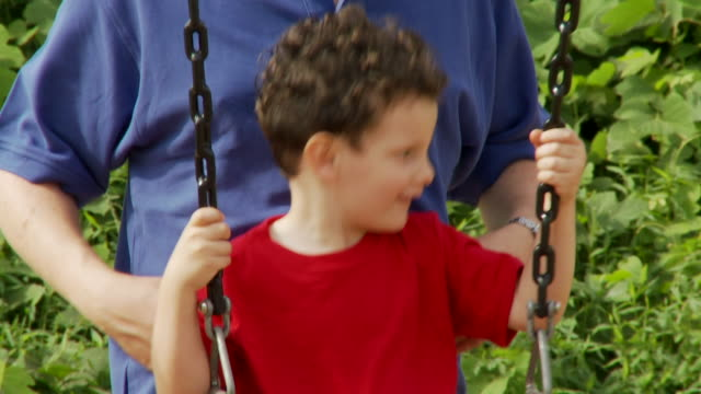 CU SLO MO TD Father pushing son (2-3) on swing / Atlanta, Georgia, USA