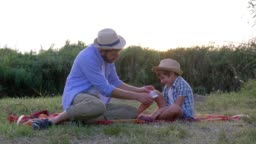 father puts a tight bandage on injured knee of the son sitting on the rug during a family weekend at sunset