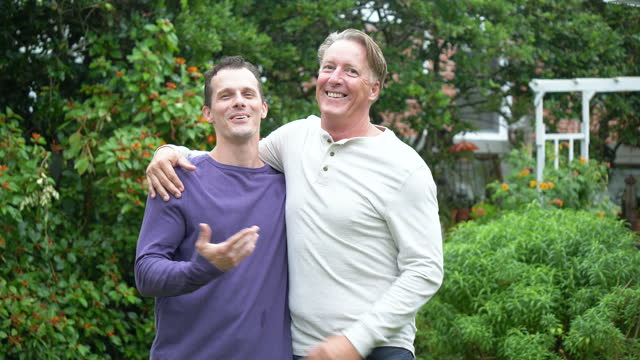 father puts arm around son's shoulder smiling in backyard - mid adult men stock videos & royalty-free footage