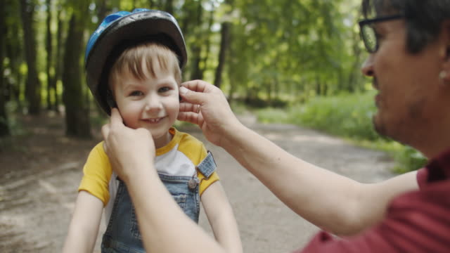 father putting bike helmet on his son's head - cycling helmet stock videos & royalty-free footage
