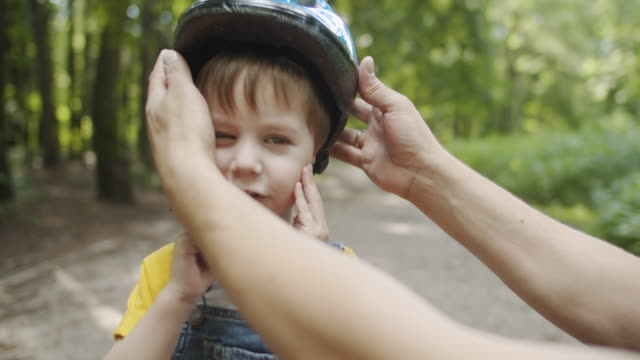 father putting bike helmet on his son's head - sports helmet stock videos & royalty-free footage