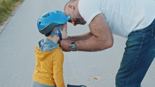 ms slo mo father putting crash helmet on sons head - casco da motociclista video stock e b–roll