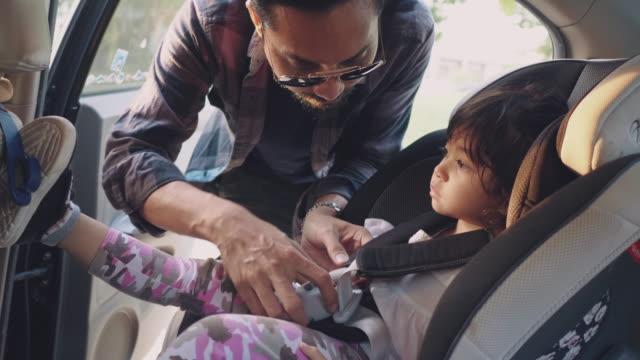 vidéos et rushes de père mettant la fille dans le siège de sécurité sur la voiture vont à l'école. - famille avec un enfant
