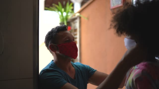 father putting face mask on daughter and embracing her before she goes to school - leaf stock videos & royalty-free footage