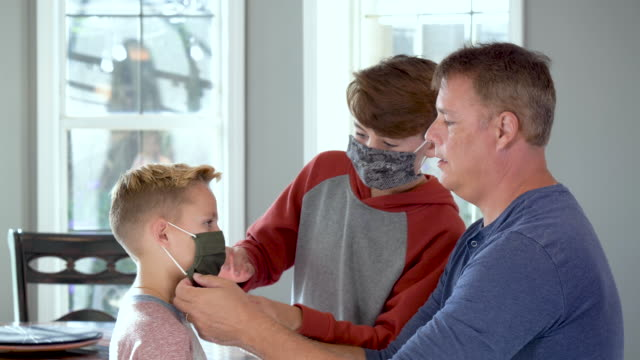 father putting face mask on son, brother helping - 8 9 years stock videos & royalty-free footage