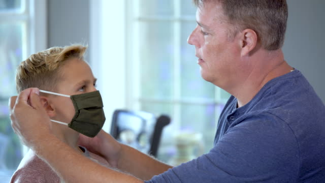 father putting face mask on son - 8 9 years stock videos & royalty-free footage