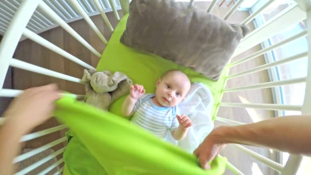 pov father putting his baby in the crib and he spills - arm stock videos & royalty-free footage