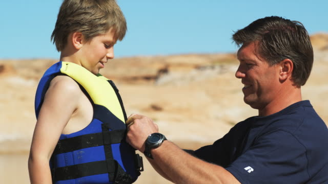 father putting life jacket on his son - flytväst bildbanksvideor och videomaterial från bakom kulisserna