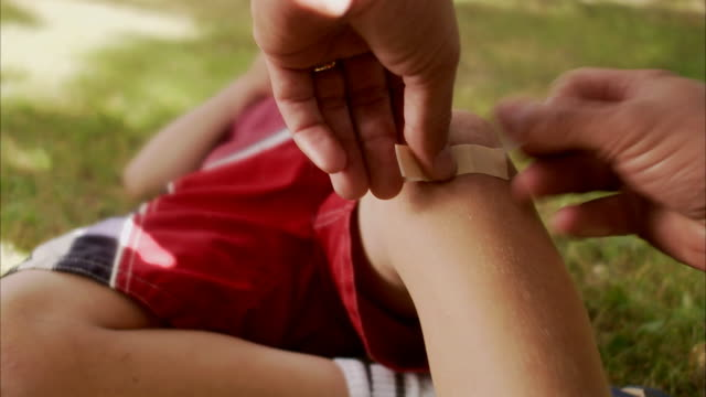 a father putting on a plaster on the knee of his son sweden. - wounded stock videos & royalty-free footage
