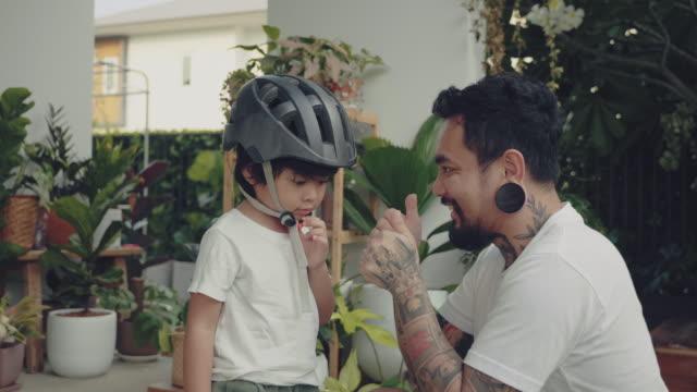 vídeos de stock, filmes e b-roll de pai colocando capacete do filho. - capacete esportivo