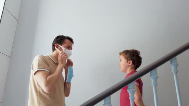 vídeos de stock e filmes b-roll de father putting protective face mask on his child before going outdoors - máscara cirúrgica