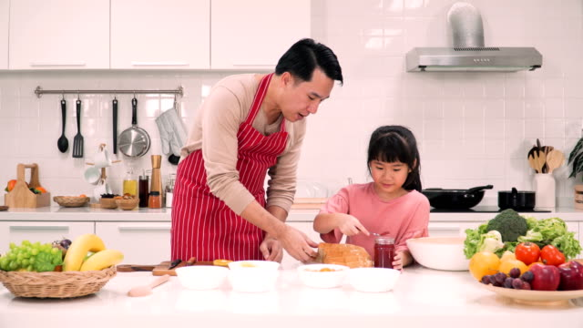 father putting strawberry jam on bread sheet for daughter - strawberry jam stock videos & royalty-free footage