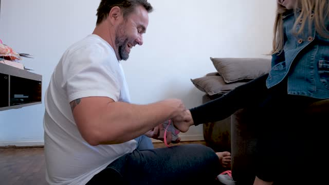 father putting tennis shoes on his daughter - genderblend stock videos & royalty-free footage