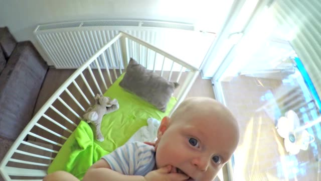 POV Father raising his baby boy out of the crib