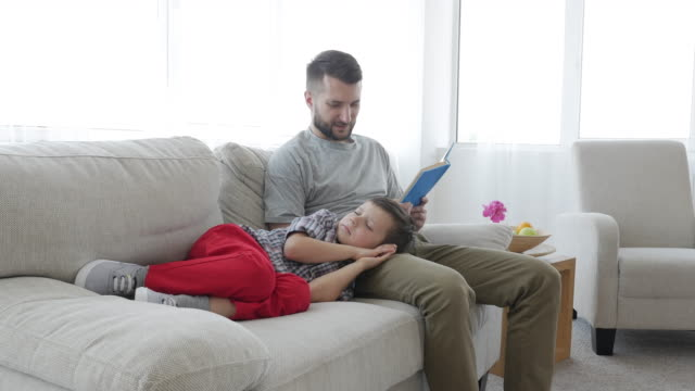 father reading a bedtime story to his young son - time stock videos & royalty-free footage
