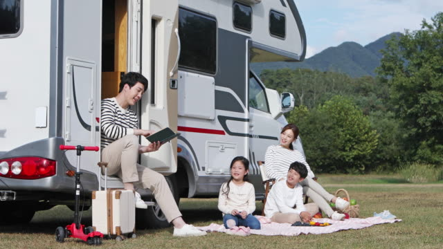 father reading a book for children in front of camper trailer on the camping grounds - camper trailer stock videos and b-roll footage