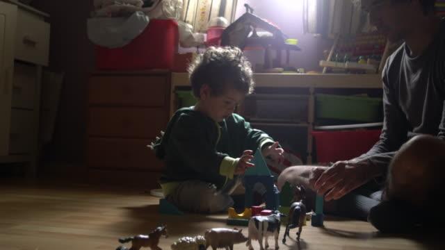 vídeos de stock, filmes e b-roll de a father reading a tale to his little son. - bloco de construção