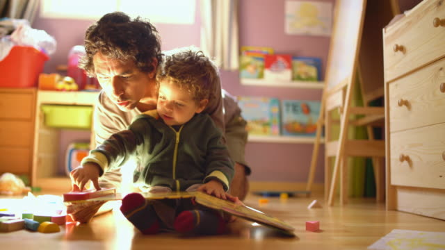 A father reading a tale to his little son.