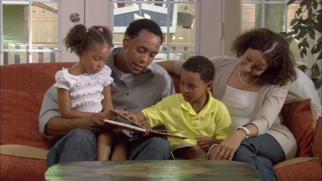 vídeos y material grabado en eventos de stock de ms, father reading book to son (6-7) and daughter (4-5) sitting on sofa, westfield, new jersey, usa - en el regazo