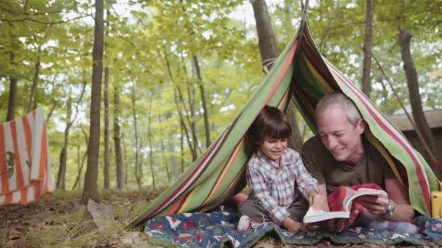vídeos y material grabado en eventos de stock de father reading book to son in blanket tent - tienda de campaña