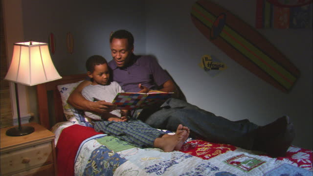 vidéos et rushes de ms, father reading book to son (6-7) sitting on bed, westfield, new jersey, usa - famille avec un enfant